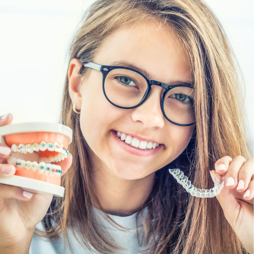 young girl smiling with Invisalign in hand