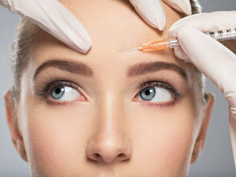 Portrait of young Caucasian woman getting cosmetic injection of botox in forehead. Beautiful woman gets botox injection in her face.