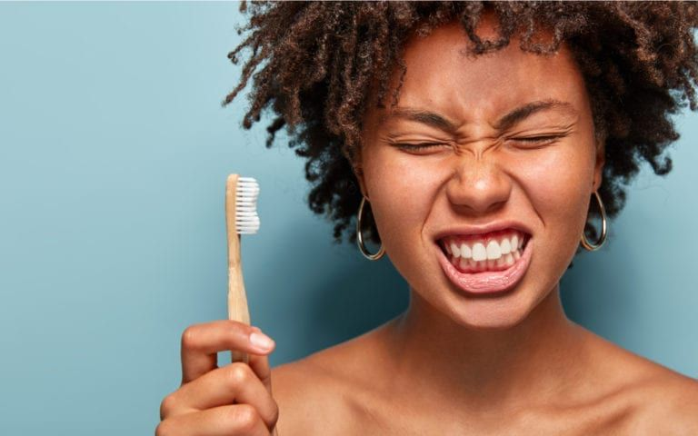 Woman with toothbrush making pained face